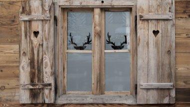 Ξύλινα παντζούρια με αντανάκλαση στο παράθυρο