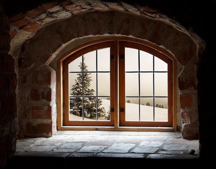 Ξύλινο παράθυρο με θέα σε χιονισμένο τοπίο